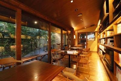 1階のカフェスペース。壁一面がブックシェルフになっていて、まるで高級旅館のライブラリーのよう。外に見える木々の緑にも癒される