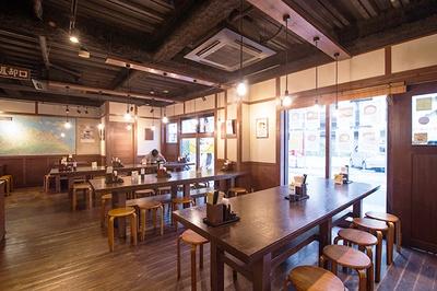 """木を基調とした店内。奥の壁には、""""うどん県""""ならでは店舗数の多さを示す香川県の地図が飾られている"""