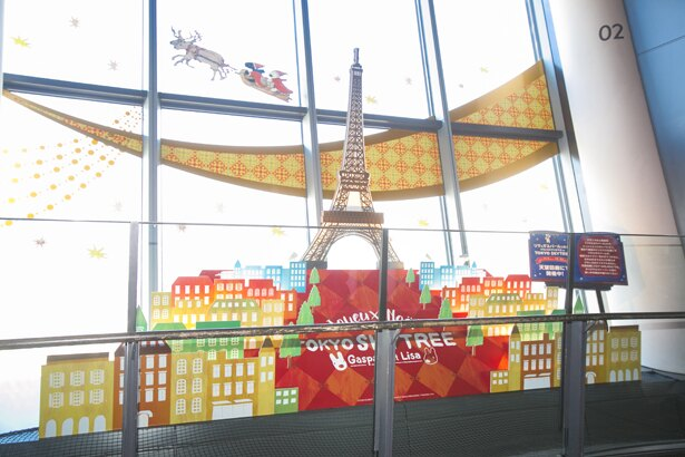 【写真を見る】パリのエッフェル塔のオブジェ。空には、サンタクロースになってソリに乗るリサとガスパールの姿も