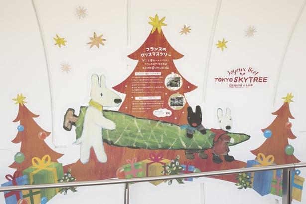 """家族といっしょにツリーを運ぶリサとガスパールが描かれている。本国フランスで""""ツリー選び""""は大人も子どもも楽しみにしている一大イベント"""