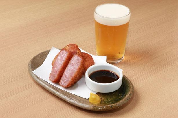 分厚くカットされた「雲仙ハム」(600円)はビールのアテにピッタリ。料理を一品以上注文するとグラスビールが一杯無料になる
