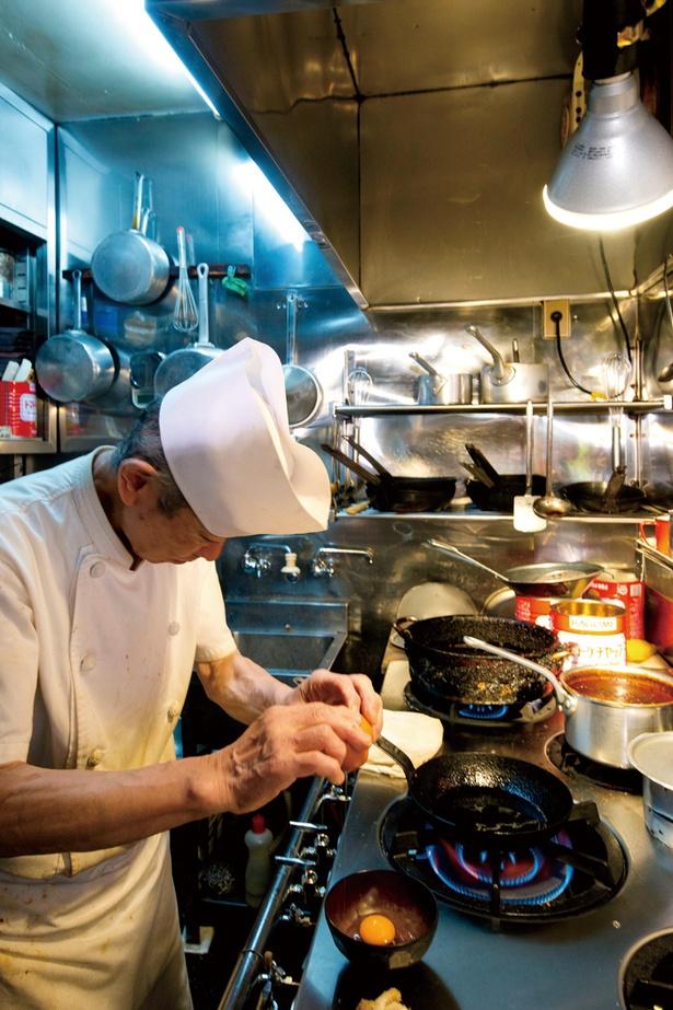 【写真を見る】古いながらもピカピカに磨かれた厨房で、次々と注文をこなす大友シェフ