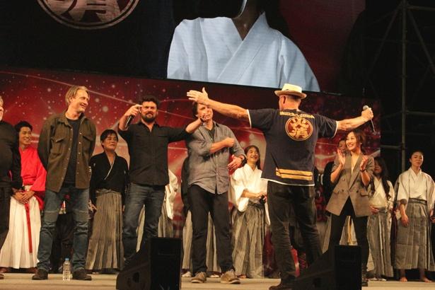 バックに「火消」と書かれたTシャツを披露して、会場の爆笑を誘ったマイケル・ルーカ―