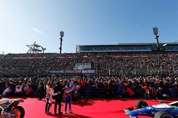 八郷本田技研工業社長を中心に、チャンピオンドライバーが満員のスタンドに手を振る