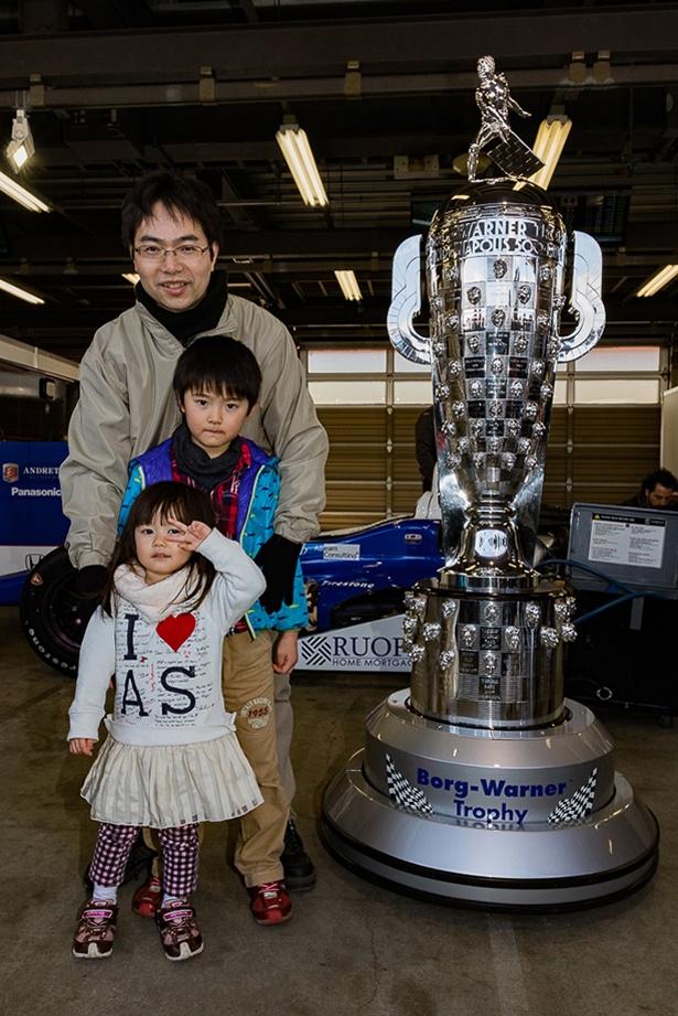 【写真を見る】時価総額4億円のインディ500優勝トロフィーと一緒に記念撮影も!