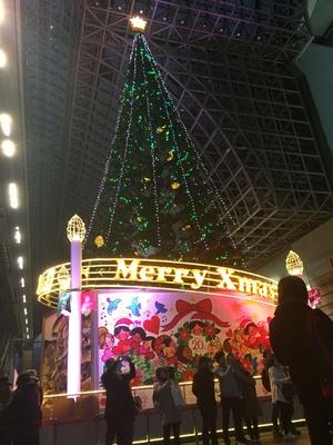 ツリーや大階段の写真を撮る人がいっぱい。台座には京都駅ビル20周年のスローガン「感謝」「未来」を表現したデザインが施されている。