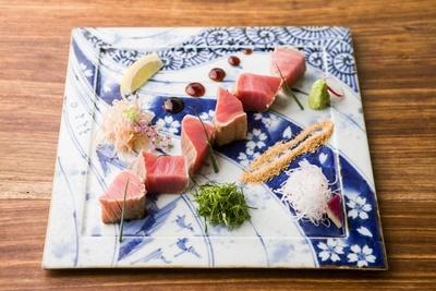 【写真を見る】「名物 マグロ藁焼き」(1380円)。藁で瞬間燻製をかけることで旨味をギュッと凝縮
