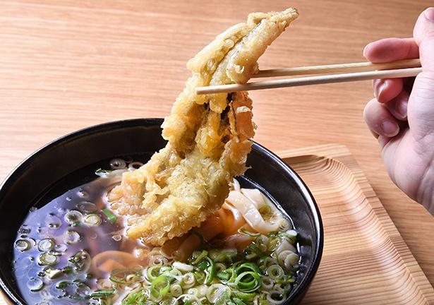 【写真を見る】見た目のインパクトもある「首切り穴子一本揚げ」。アナゴ一匹を丸ごと使った天ぷらが、器いっぱいに覆う