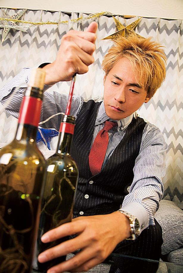 【写真を見る】ワインボトルイルミネーション作りに挑戦するヒロシさん。ボトルの中にグイグイとケーブルを押し込んで…