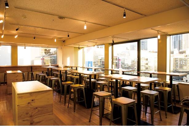 木のテーブルが配されたシンプルな内観。窓からは横浜の街並みを臨む
