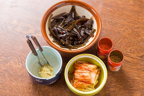 卓上の薬味は自家製のキムチと昆布の佃煮、しょうが、一味唐辛子と七味唐辛子を用意する