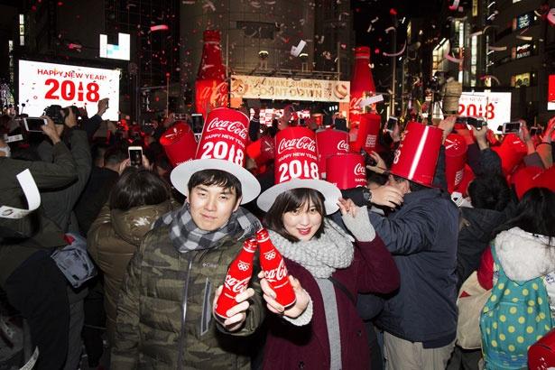 「コカ・コーラ」で乾杯し、新しい年の訪れを祝うカップル