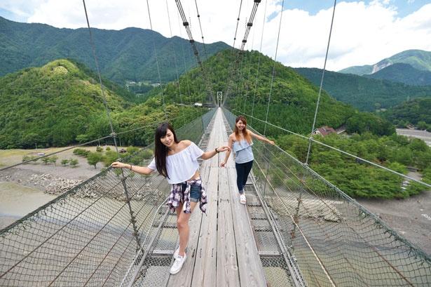 【写真を見る】1954年に完成。足元に十津川が流れ、スリル満点のつり橋。GWとお盆は一方通行のためシャトルバス(¥200)を運行する。