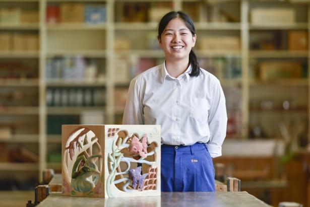 高文連に出品した作品「アラウンド」と宮田さん。箱の中央にたんぽぽの花が1輪あり、それを囲むように彫刻が施されている