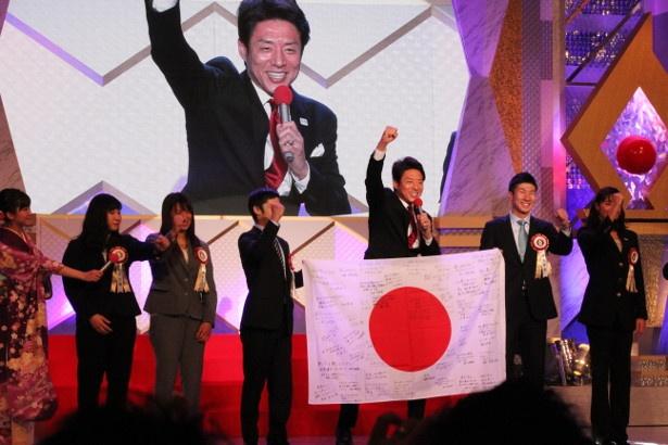 選手たちからのメッセージが書かれた日の丸を掲げ、スポーツ界にエールを送る松岡修造