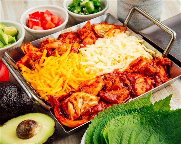 【写真を見る】甘辛く味付けされた肉や野菜、トッポギを、トロトロのチーズに絡めて味わおう!