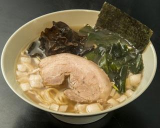 「ヤキニク・ラーメン フタバ」のラーメン(700円)。半濁豚骨スープに太麺。肉厚豚バラ、刻みタマネギ、ワカメ、黒キクラゲを盛る