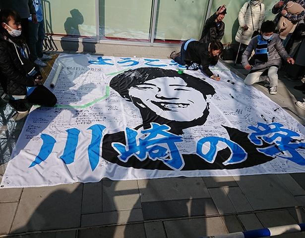 【写真を見る】会場となった「カルッツかわさき」の前では移籍加入の齋藤 学選手へファンが寄せ書きをした