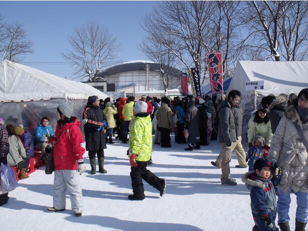 【写真を見る】熱々の食べ物を求める人々で会場内に並ぶテント屋台はいっぱい