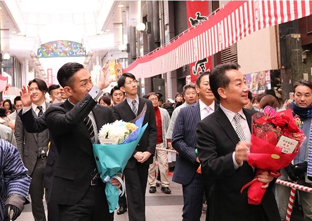 【写真を見る】街頭に集まった5000人のファンに手をふり、博多到着のごあいさつ