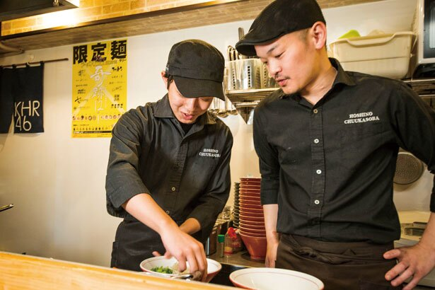 店主の樋上さん(右)はサポート役に回り、高谷くんの作業を温かい目で見守る