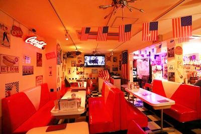 アメリカ国旗などが飾られる店内。広いソファー席のほか、カウンターも