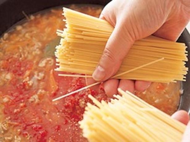 スパゲッティはソースの水分でゆでていく。半分に折って加えることで、フライパンからはみ出さず、効率よくゆでられる。
