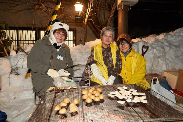 ボランティアでお餅とジャガイモを焼いている、池田さん(左)、尾崎さん(中)、山口さん(右)