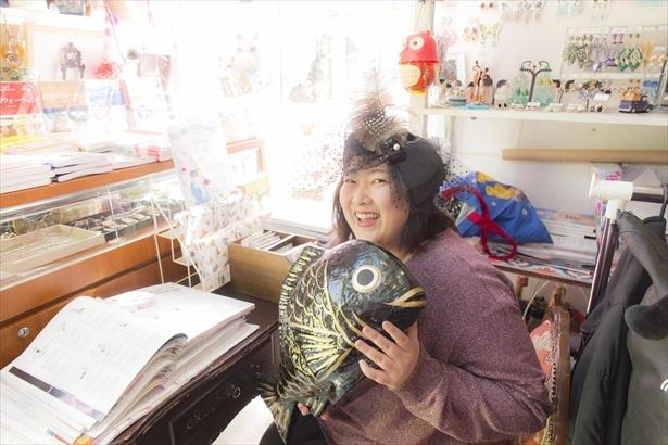 【写真を見る】開運アイテムである鯛の置物を手に笑顔!