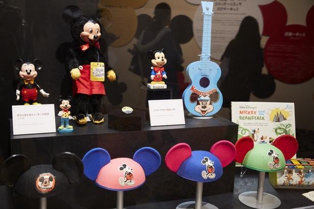 懐かしい表情のミッキーアイテムやイヤーハットの展示。黄色い服を着た陶器の人形は日本製
