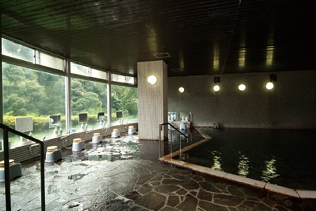 浴槽に青石を配した露天風呂「滝の湯」の内湯。壁を湯が流れる