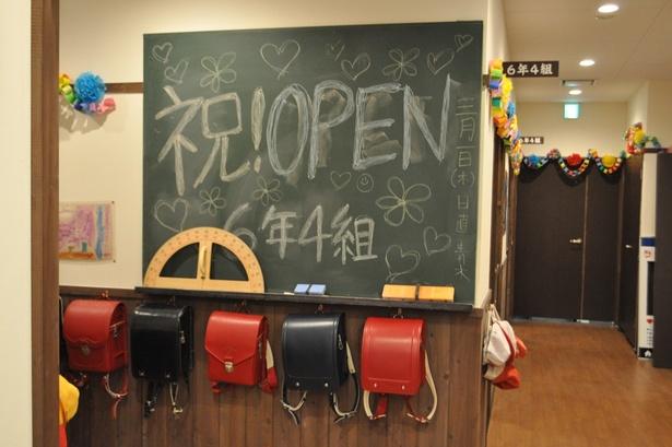 """店の入口には、""""学校居酒屋""""らしく元気な文字が書かれた黒板がある"""