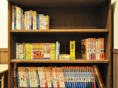 廊下の本棚には、「ズッコケ三人組」や「学研まんが」など学校にありがちな本が…