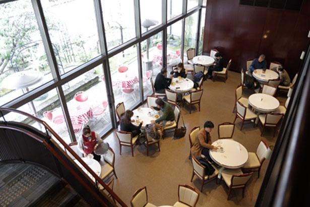 【写真を見る】一面のガラス窓から中庭が望める別館1階/イノダコーヒ本店