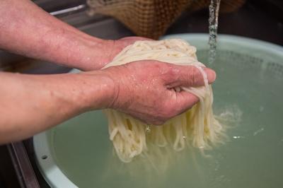 【写真を見る】店内の一角に置かれた製麺機を使い、店主の田中さんが麺を製造。茹でたてを提供するため、時に15分ほど時間がかかることもある