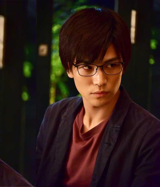 【写真を見る】黒縁メガネが新鮮!ジャーナリストらしい真剣な眼差しを見せる岩田剛典