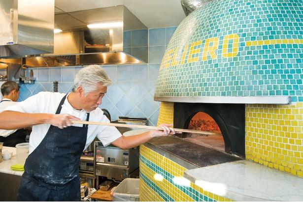 開放的なオープンキッチンではナポリの職人に特注で作ってもらった自慢のピザ窯でオーナー自らピザを焼く姿が見られる