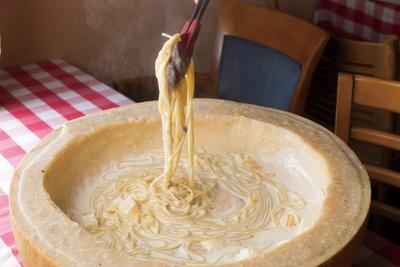 【写真を見る】「チーズカフェ」の「24ヵ月熟成パルミジャーノ・レッジャーノ焦がしパスタ」(1,814円)。大きなチーズの中でパスタを仕上げていくパフォーマンスも