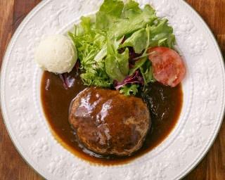王道人気の「自家製ハンバーグ デミグラスソース」。皿の上にサラダが添えられ、ランチは1200円でライスお代わり自由、夜は1404円で食べ放題のライスかパンを選べる
