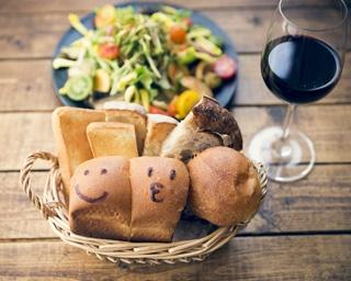 「パンとワイン 麻布FLAT」の「自家製手づくりパン」¥540(おかわり自由)。グラスワイン¥540~。奥は「八ヶ岳直送!! 有機野菜盛りサラダ」¥885