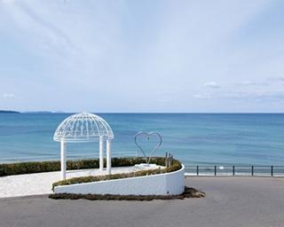 「オテル グレージュ」。空と海の青のコントラストは爽快な美しさ。手前にあるのは「幸福の鐘」