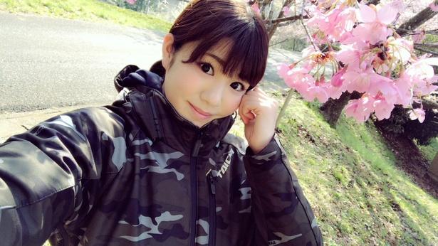 【写真を見る】河津桜と、キュートにポーズを決める梅本まどか