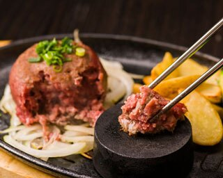 「爆弾バーガー  」1500円(税抜)。インパクト抜群のハンバーガーは厚さ5cmの塊肉と、はみ出る大きなベーコンが目を引く