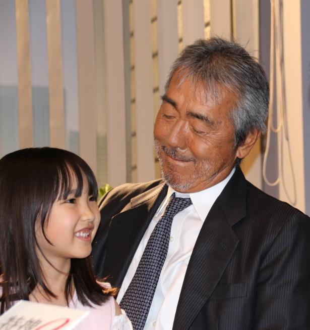 娘役の庄野凛を抱きかかえ、笑顔の寺尾聰