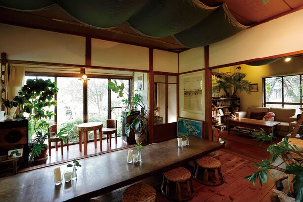 「RUSTIC BARN」。店内はローテーブル、座椅子席がメインで大きな革張りソファも。庭は大きなパルムの木が印象的