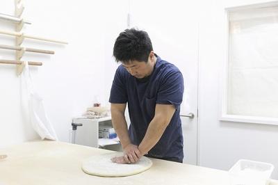 店内の製麺室で麺を打つ店主・佐藤さん。全身の力を使って何度もこねることで強いコシが生まれる