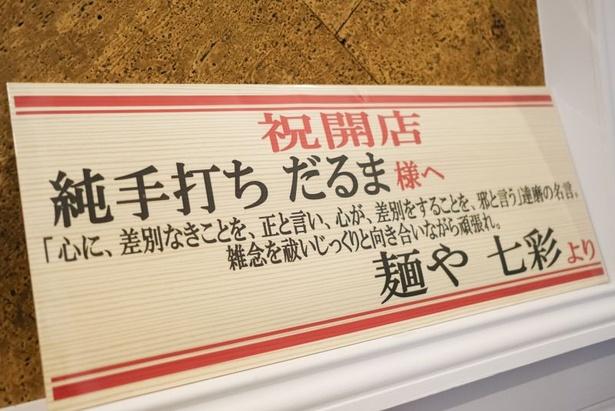 【画像を見る】店内の一角には修業先の「麺や 七彩」から開店祝いに贈られたメッセージが飾られている