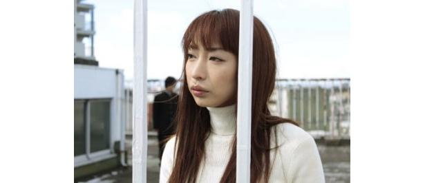 屋上に立ち、物憂げな表情で遠くを見つめる優子