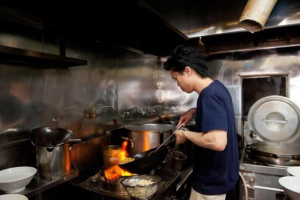 【写真を見る】ビートを刻むようにリズミカルに鍋を振る店主の幸田啓さん