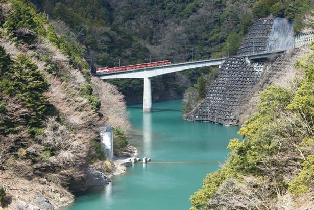 急勾配の橋を上るアプト式列車。高さ109mの巨大な長島ダムを一望できる